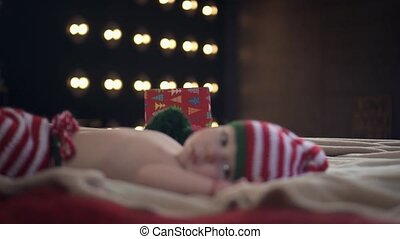 Little baby in striped cap and pants is lying on bed and looking up to camera while his mother brings a present box on the background