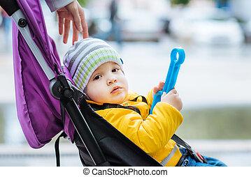 Little baby is sitting in a stroller