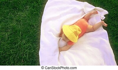 Little baby laying on the towel on the grass, top down view...