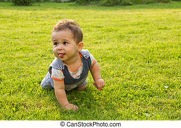 little baby learning to crawl on the grass a Sunny summer day. the concept children's development by months. happy child playing in the Playground