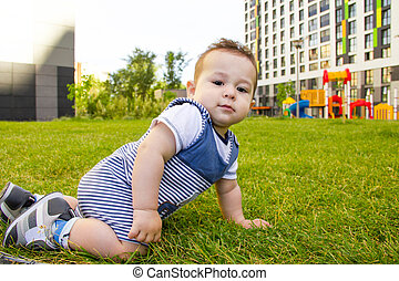 little baby learning to crawl on the grass a Sunny summer day. the concept of children's development by months. happy child playing in the Playground