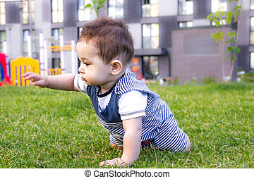 little baby learning to crawl on the grass on a Sunny summer day. the concept of children's development by months. happy child playing in the Playground
