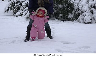 Little baby learning to walk. Woman with her toddler girl at winter park. 4K