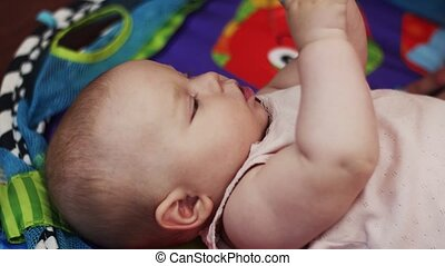 Little baby lie in crib playing with toys, holding in mouth. Child. Motherhood.