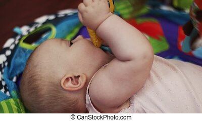 Little baby lie in crib playing with toys, holding in mouth. Cute. Motherhood.