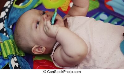 Little baby lie in crib playing with toys, holding in mouth. Motherhood.