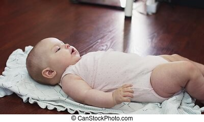Little baby lie on floor in apartment. Child. Playing. Cute. Family.