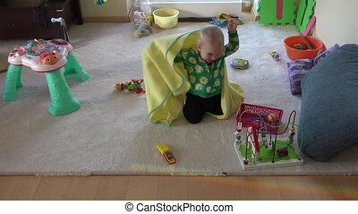 little baby play with wrap at room. Happy childhood games....