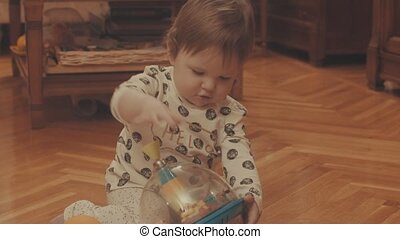 Little baby playing on the floor with a whirligig