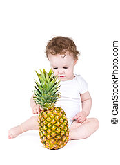 Little baby playing with a big pineapple