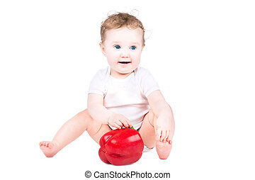 Little baby playing with a big red paprika, isolated on white