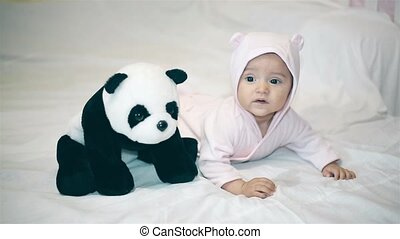 Little baby playing with a Panda on a white blanket