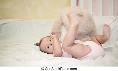 Little baby playing with a Teddy bear on a white blanket