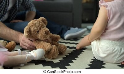 Little baby playing with soft bear at home