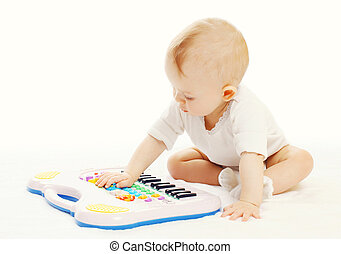 Little baby playing with toy piano on a white background