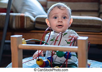 Little baby playing with wooden game at home