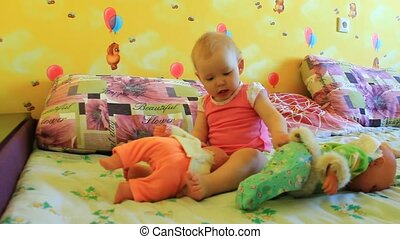 little baby plays with her dolls - little girl plays with...