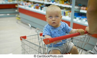 Little baby sitting in a grocery cart in a supermarket, while his father chooses purchases.