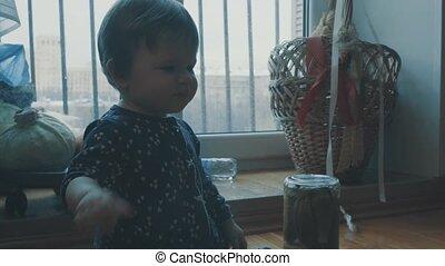 Little baby sitting in the kitchen near window, then...