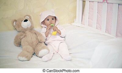 Little baby sitting next to a Teddy bear on a white blanket