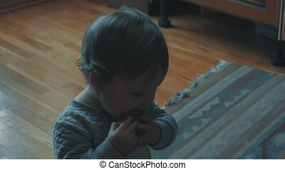Little baby sitting on the floor and eating a piece of bread
