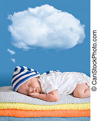 Little baby sleeping on stack of colorful towels with a...