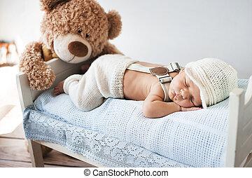 Little baby sleeping with a teddy bear