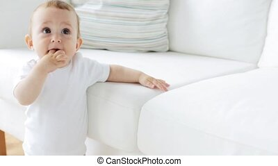 little baby standing and holding to sofa at home 24