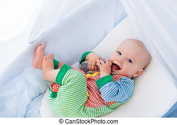 Little baby with bottle in white bed - Funny baby in...