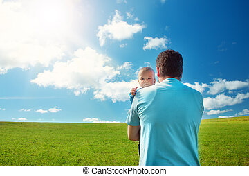 Little baby with father standing in the field