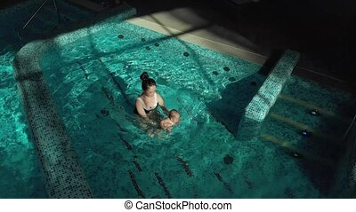 Little baby with mother swimming