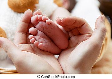 Little baby's feet in mother's hands