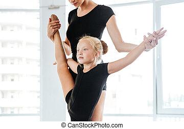 Little balerina stretching legs with her teacher in ballet...
