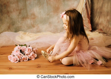 Adorable little girl dressed as a ballerina in a tutu, tying her ballet slippers.