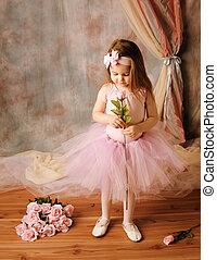 Little ballerina beauty holding a pink rose