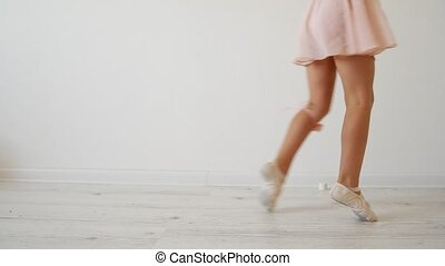 Little ballerina dancing on a white background. Attempt to dance on fingers.