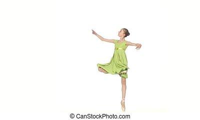 little Ballerina in green dress posing on a white. slow motion