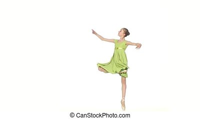 little Ballerina in green dress posing on a white. slow motion
