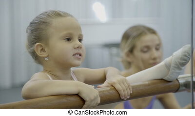 Little ballet dancer stretching her leg on the barre and learns how to lean right.