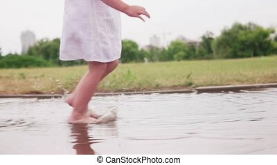 Little barefoot girl running through puddles in white dress...
