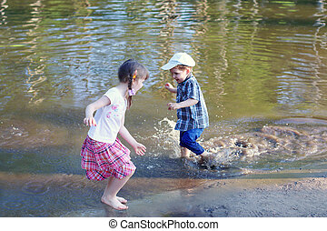 Little barefoot girl with boy laugh and run in water of pond at summer day