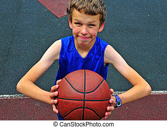 Little basketball player preparing for throwing ball