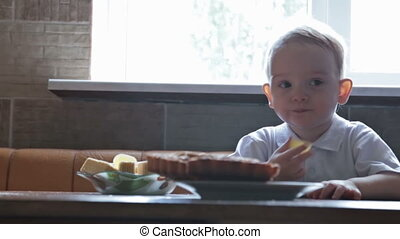 Little beautiful blond boy eating pie at the kitchen