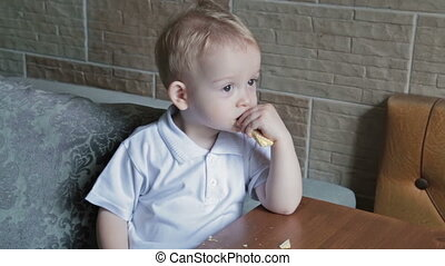 Little beautiful blond boy eating wafer at the kitchen