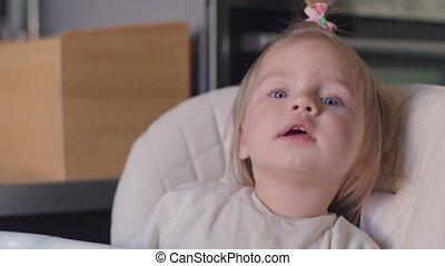 Little beautiful blonde smiling girl poses faces closeup.