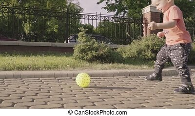 Little beautiful boy playing with ball in the park. Slow motion