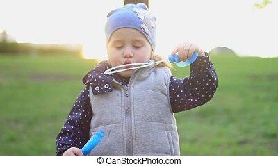 Little beautiful girl blowing bubbles