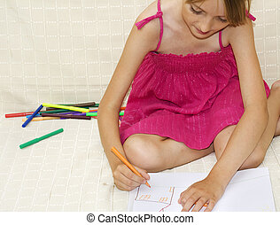 Little beautiful girl drawing on sofa