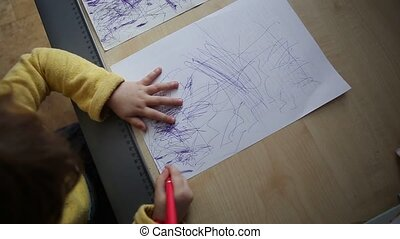 Little beautiful girl draws at the desk