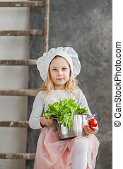 Little beautiful girl holding a pot full of vegetables. Healthy food. Harvest. Little housewife